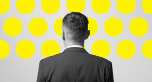 Man standing and watching to the wall with many yellow circles title=
