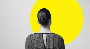 Woman standing and watching to the wall with one yellow circle title=