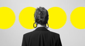 Man standing and watching to the wall with three yellow circles title=