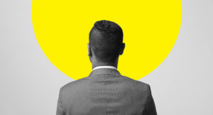 Man in suit standing and watching to the wall with one yellow circle title=